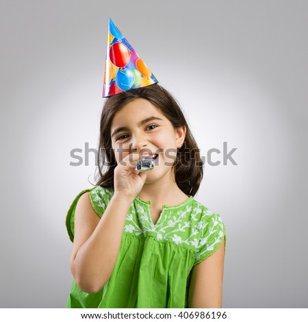 Studio portrait of a little girl wearing a party hat on her birthday - stock photo