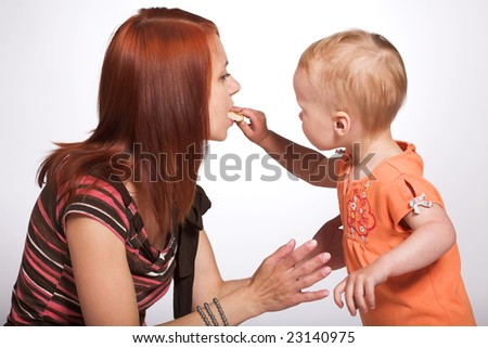 Studio portrait of a little girl who feeds her mother with a cake - stock photo