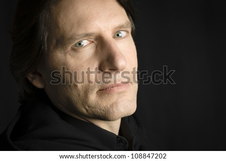 Studio Portrait of a man with an intense look staring directly to the camera - stock photo