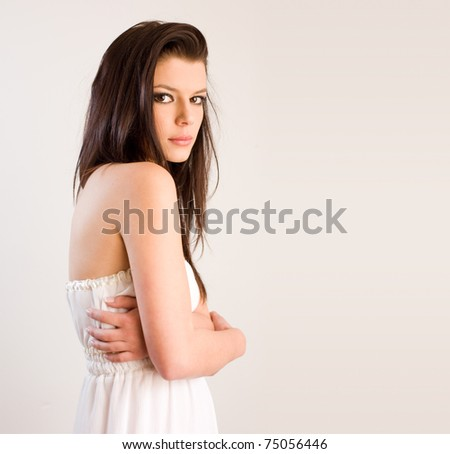 Studio portrait of a romantic looking shy brunette beauty with copy space.