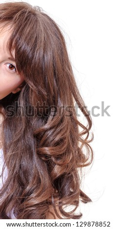 Studio portrait of a seductive young woman with beautiful long wavy brunette hair peering around the edge of the frame with one eye looking at the camera - stock photo