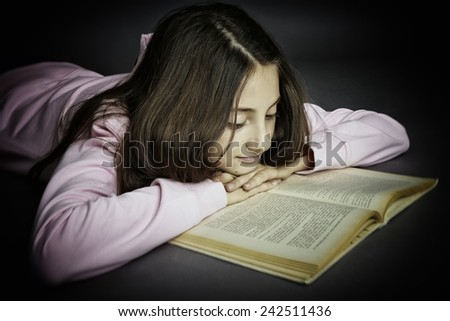 Studio portrait of a smiling schoolgirl reading a book while lying on the floor, gray background. - stock photo