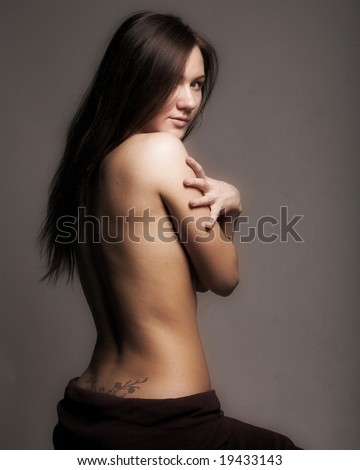 Studio portrait of a topless modest girl in semidarkness