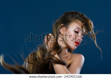 Studio portrait of a woman. Wind generator is directed to long hair. - stock photo