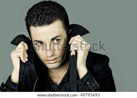 Studio portrait of a young adult worried man looking aside, with a mysterious expression