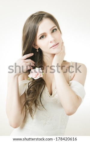 Studio portrait of a young beautiful bride in a white dress. Professional make-up and hairstyle with flowers. - stock photo