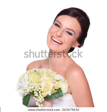 Studio portrait of a young beautiful bride with a wedding bouquet. Professional make-up and hair-style. - stock photo