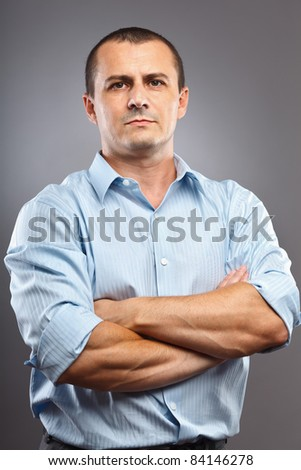 Studio portrait of a young businessman, with his arms folded - stock photo