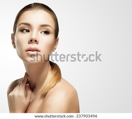 Studio portrait of a young European woman with clear healthy perfect skin on a gray background. Beauty model woman face - stock photo