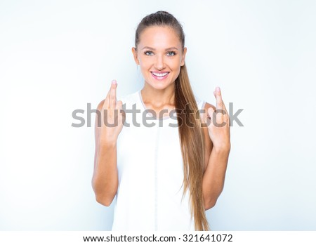 studio portrait of a young happy smiling girl . studio photoshoot. isolated on white . crossed fingers. beauty model - stock photo