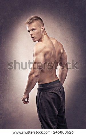 studio portrait of a young man in the bodybuilder pose - stock photo