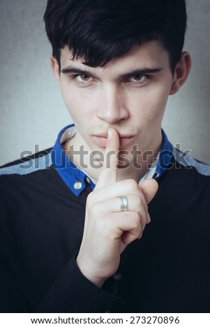 Studio portrait of a young man making a silence gesture, gray background - stock photo