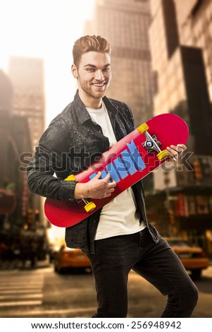 Studio portrait of a young man posing with a skateboard on street of New York - stock photo