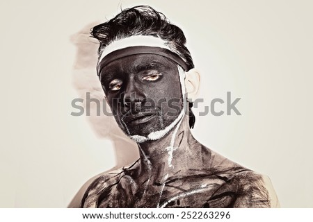 Studio portrait of a young man with a black theatrical makeup on white background - stock photo