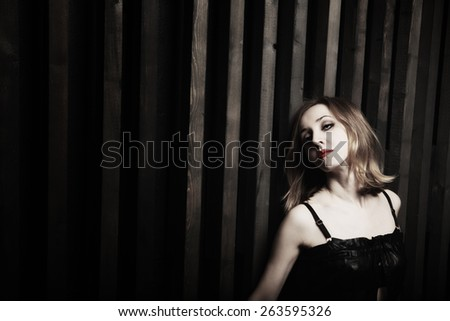 Studio portrait of a young passionate woman against a wooden wall - stock photo