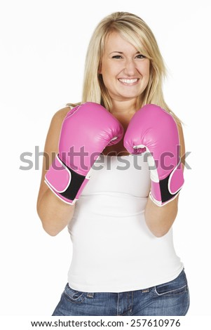 Studio portrait of a young smiling blonde woman wearing pink boxing gloves on a white background. - stock photo