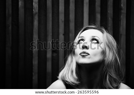 Studio portrait of a young woman against a wooden wall - stock photo