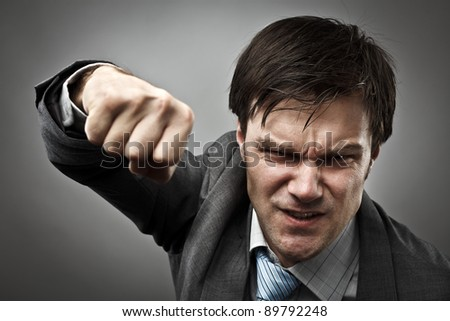 Studio portrait of an aggressive businessman punching - stock photo