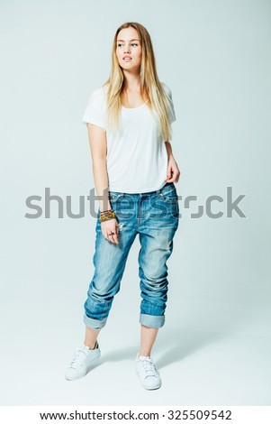 Studio Portrait of an attractive young woman in jeans - stock photo