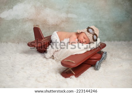 Studio portrait of an eight day old newborn baby boy wearing an aviator cap with goggles. He is sleeping on a vintage inspired airplane posing prop. - stock photo