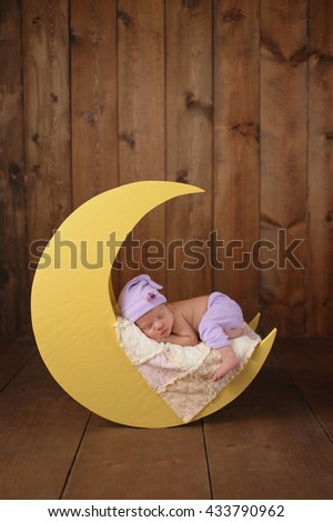 Studio portrait of an eleven day old newborn baby girl wearing pajama bottoms and a sleeping cap. She is sleeping on a moon shaped posing prop. - stock photo