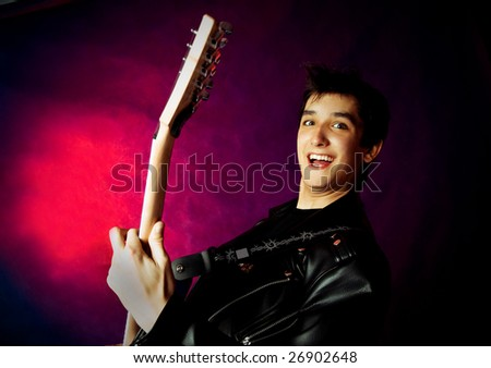 studio portrait of an excited young man playing a guitar - stock photo