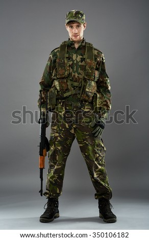 Studio portrait of an young soldier in uniform with machine gun, over gray background - stock photo