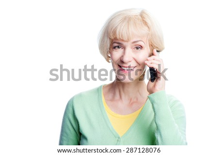 Studio portrait of attractive blond middle age woman talking by smart phone. Isolated on white. - stock photo