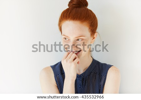 Studio portrait of attractive young Caucasian redhead female looking away with cute and shy smile. Pretty student girl with freckles and ginger hair smiling with shy expression Youth skin care concept - stock photo