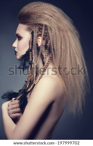 Studio portrait of attractive young woman with creative bright makeup and hairstyle with black feathers  - stock photo