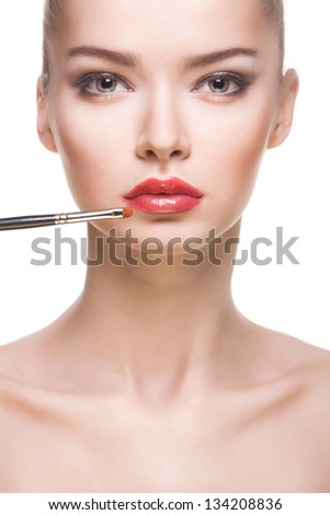 studio portrait of attractive young woman with lips-brush on white background - stock photo