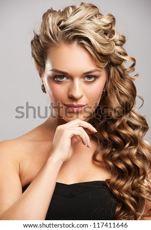 Studio portrait of attractive young woman with long blond hair and beautiful stylish hairstyle