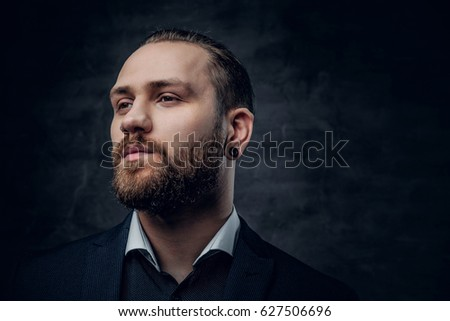 Studio portrait of bearded male dressed in a blue jacket over grey vignette background.