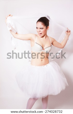 Studio portrait of beautiful angry bride wearing in a veil, against gray background - stock photo