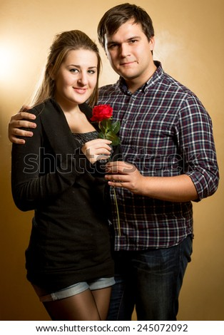 Studio portrait of beautiful couple in love hugging and looking at camera - stock photo