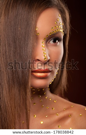 studio portrait of beautiful female woman with futuristic cristal makeup looking up