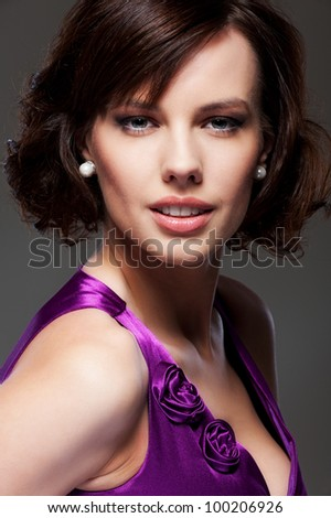 studio portrait of beautiful smiley brunette over dark background