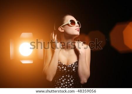 Studio portrait of beautiful woman with bright spotlight over black background - stock photo