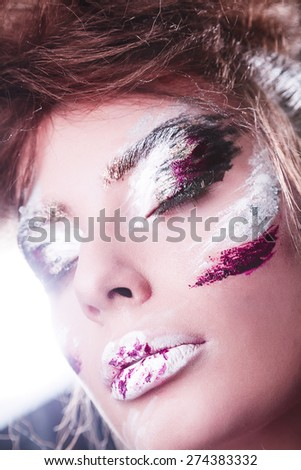 Studio portrait of beautiful woman with creative make-up