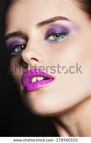 Studio portrait of beautiful woman with professional make up on black background - stock photo