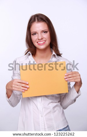 Studio portrait of beautiful young business woman holding paper on Business and Finance theme/Lovely successful business woman holding a banner for your special text