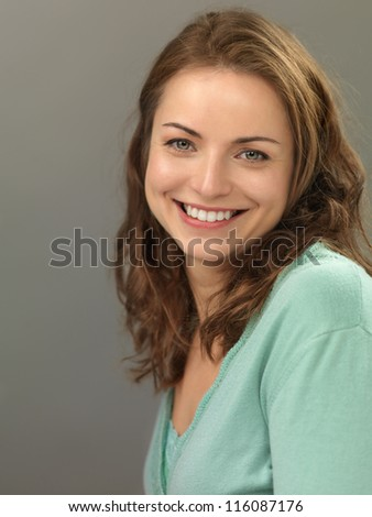 studio portrait of beautiful, young woman, smiling, on gray background