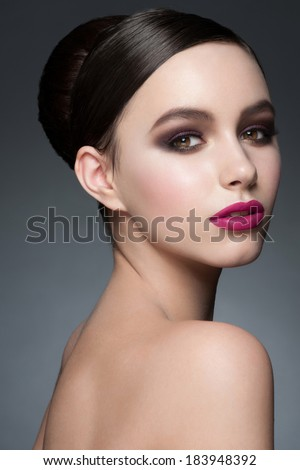 Studio portrait of beautiful young woman with stylish bright makeup and hairstyle - stock photo