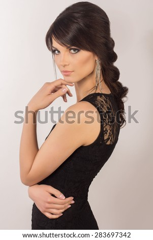 Studio portrait of beautiful young woman with stylish bright makeup and hairstyle