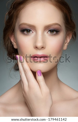 Studio portrait of beautiful young woman with stylish makeup and manicure - stock photo