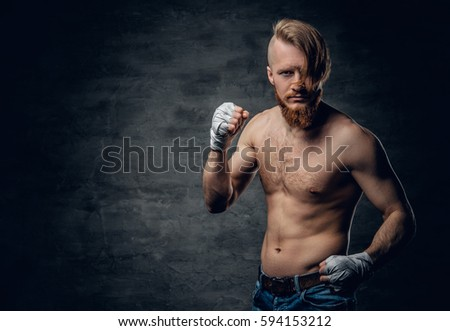 Studio portrait of brutal bearded redhead fighter with long hair over dark grey background.
