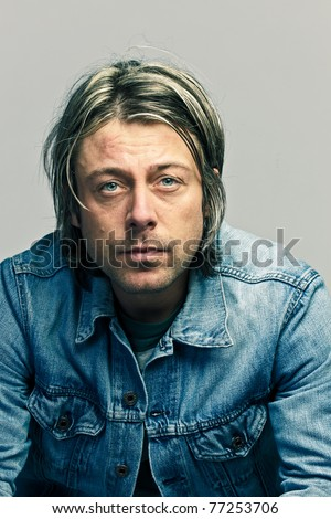 Studio portrait of casual young man with long blond hair wearing jeans jacket cool looking. - stock photo