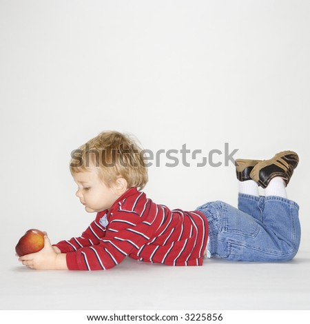 Studio portrait of Caucasian boy holding apple against white background. - stock photo