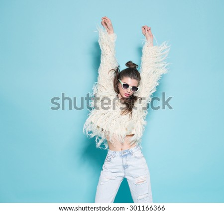 studio portrait of cheerful fashion hipster girl going crazy making funny face and dancing. Blue color background. - stock photo