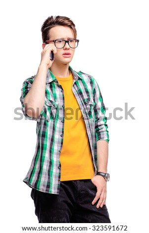 Studio portrait of confused young man talking on mobile phone. Isolated on white. - stock photo